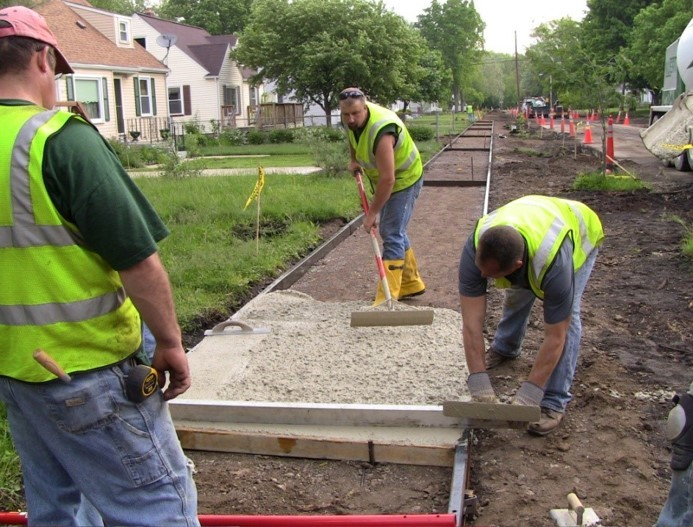 City crews pave a sidewalk